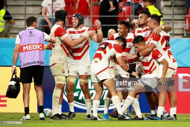 Kenki Fukuoka of Japan celebrates with teammates after scoring his team's third try during the Rugby World Cup 2019 Group A game between Japan and...