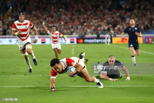 Kenki Fukuoka of Japan dives to score their third try as Scotland player Stuart Hogg reacts during the Rugby World Cup 2019 Group A game between...