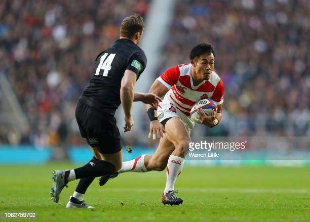 Kenki Fukuoka of Japan runs with the ball under pressure from Chris Ashton of England during the Quilter International match between England and...