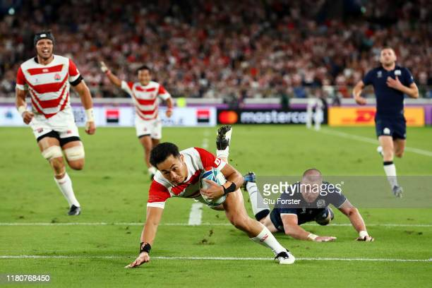 Keita Inagaki of Japan touches down to score their third try as Stuart Hogg of Scotland looks on during the Rugby World Cup 2019 Group A game between...