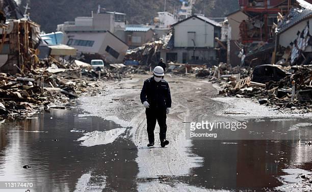 Kenkichi Sawada walks on a street damaged by a tsunami following the March 11 earthquake in Kesennuma City Miyagi prefecture Japan on Friday April 1...