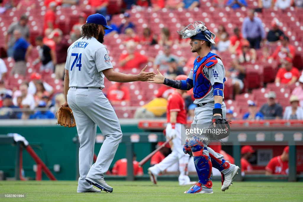 Kenley Jansen #74 of the Los Angeles Dodgers and Yasmani Grandal #9 celebrate after the final out of the 8-1 win over the Cincinnati Reds at Great American Ball Park on September 12, 2018 in Cincinnati, Ohio.