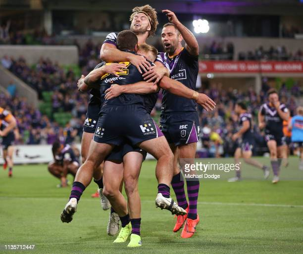Kenneath Bromwich of the Storm is hugged by Cameron Munster Christian Welch and Cameron Smith of the Storm after scoring a try during the round one...