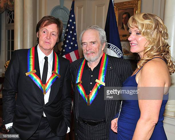 Kennedy Center honorees Sir Paul McCartney left and Merle Haggard center share some conversation after posing for their formal class photo following...