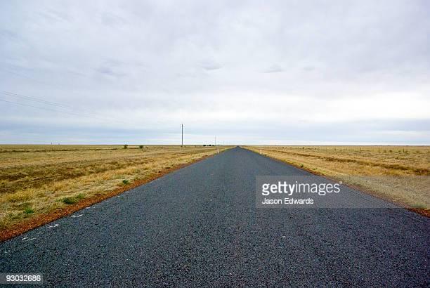 A grey storm rolls over a featureless plain and remote outback road.