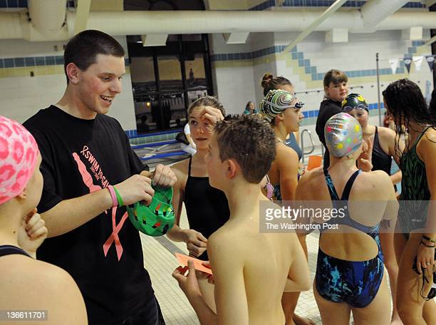 Kennedy High School senior David Collier left helps a young participant with his swim cap before racing during the Swim to Save event at Olney Swim...