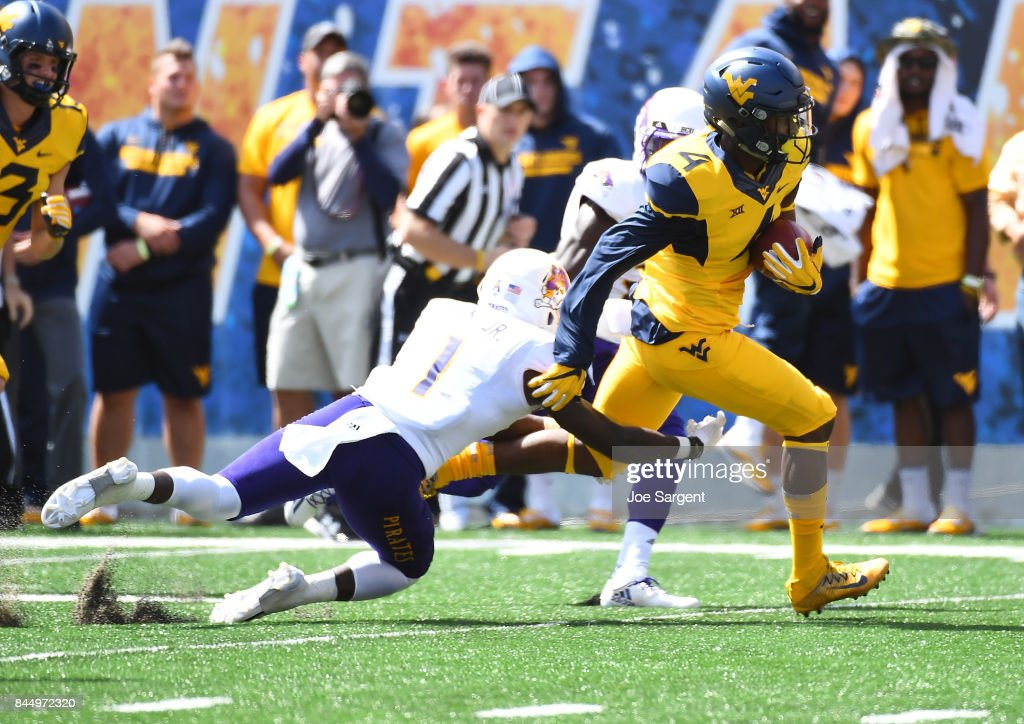 Kennedy McKoy #4 of the West Virginia Mountaineers breaks a tackle by Tim Irvin #1 of the East Carolina Pirates and runs for a touchdown during the first quarter at Mountaineer Field on September 9, 2017 in Morgantown, West Virginia.