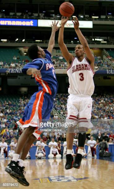 Kennedy Winston of the Alabama Crimson Tide shoots over Corey Brewer of the Florida Gators during the semifinals of the SEC Men's Basketball...
