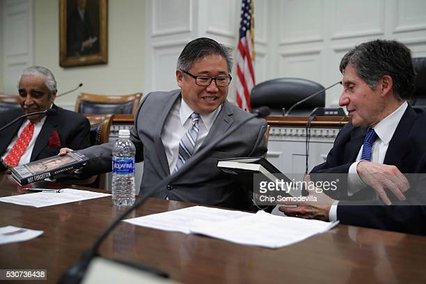 Kenneth Bae gives copies of his new book Not Forgotten to Rep Charles Rangel and Ambassador Joseph DeTrani during a panel discussion in the Rayburn...