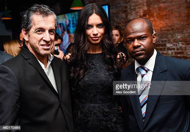 Kenneth Cole poses for a photo with Adriana Lima and Dr Marc Edson Augustin during an event for the St Luke Foundation For Haiti at Acme on December...