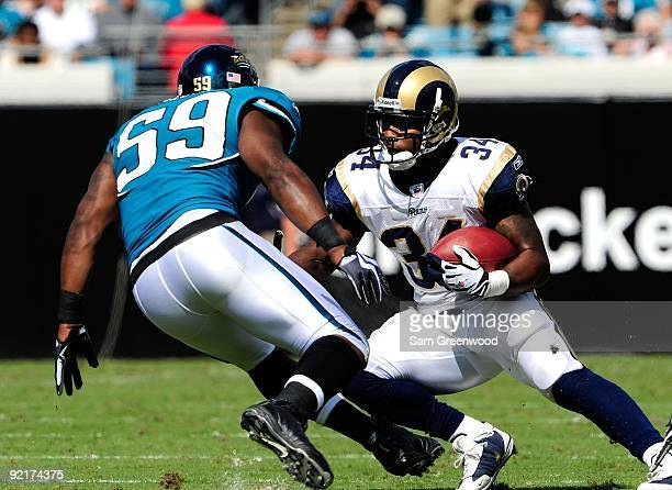Kenneth Darby of the St Louis Rams attempts to run past Brian Iwuh of the St Louis Rams during the game against the Jacksonville Jaguars at...