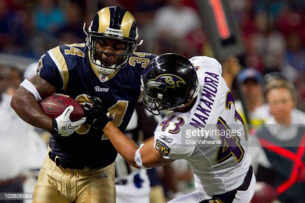 Kenneth Darby of the St Louis Rams is tackled by Haruki Nakamura of the Baltimore Ravens during an NFL preseason game at the Edward Jones Dome on...