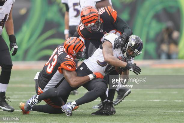 Kenneth Dixon of the Baltimore Ravens runs the football upfield against George Iloka and Carlos Dunlap of the Cincinnati Bengals during their game at...