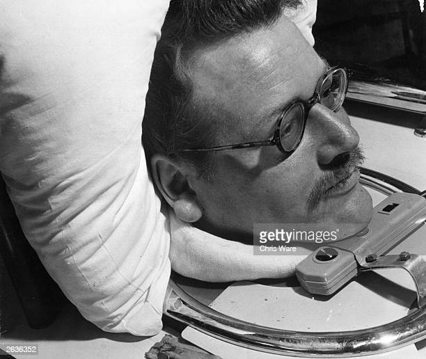 Kenneth Evans a paralysed wheelwright engineer uses a microfilm device attached to his iron lung to enable him to read books He turns the pages with...