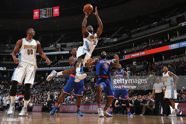 Kenneth Faried of the Denver Nuggets goes up for a shot and is fouled by Kyle O'Quinn of the New York Knicks at Pepsi Center on March 8 2016 in...