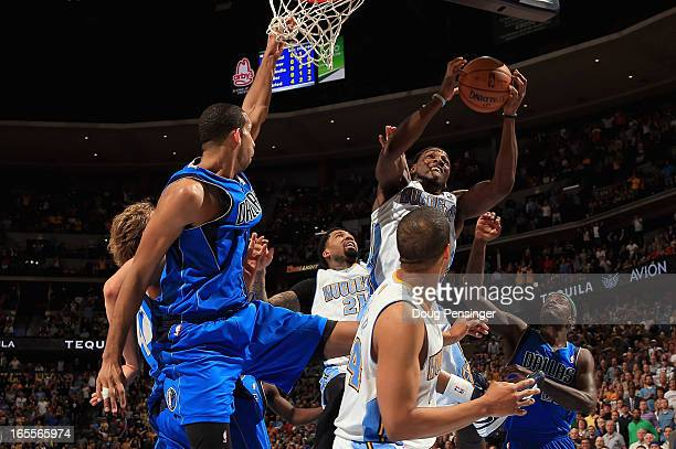 Kenneth Faried of the Denver Nuggets grabs a rebound in a crowd against the Dallas Mavericks at the Pepsi Center on April 4 2013 in Denver Colorado...