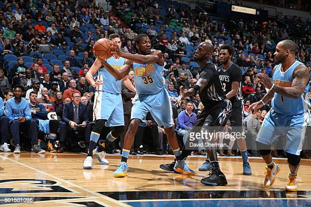 Kenneth Faried of the Denver Nuggets handles the ball against Kevin Garnett of the Minnesota Timberwolves on December 15 2015 at Target Center in...