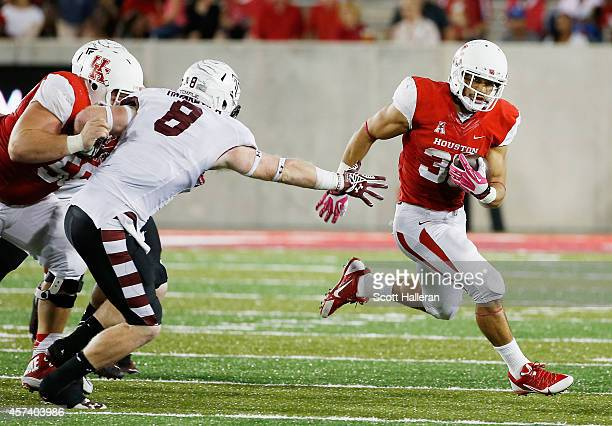 Kenneth Farrow of the Houston Cougars fights off a tackle by Tyler Matakevich of the Temple Owls in the first half of their game at TDECU Stadium on...