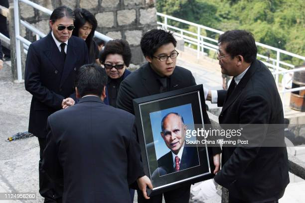 Kenneth Fok Kai-kong, grandson of Henry Fok Ying-tung, holds a portrait of late tycoon at the funeral, followed by his father Timothy Fok Tsun-ting ,...