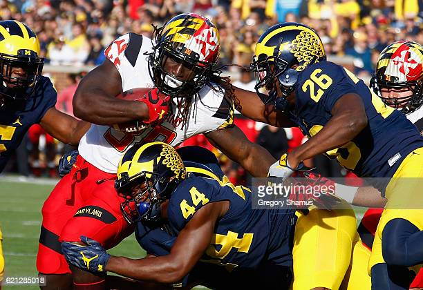 Kenneth Goins Jr #30 of the Maryland Terrapins gates tackled for a loss by Jourdan Lewis and Delano Hill of the Michigan Wolverines during the first...