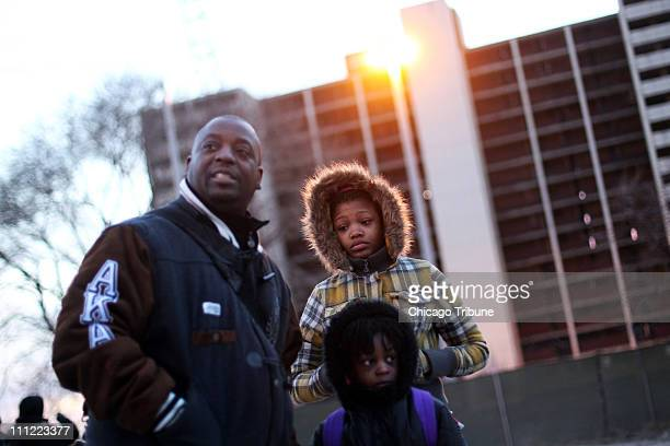 Kenneth Hammond and daughters Kentasha and Kenya watch the demolition of the last remaining CabriniGreen highrise building in Chicago Illinois on...