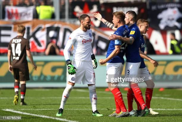 Kenneth Kronholm of Holsein Kiel celebrates with his team mates after making a save during the Second Bundesliga match between Holstein Kiel v FC St...