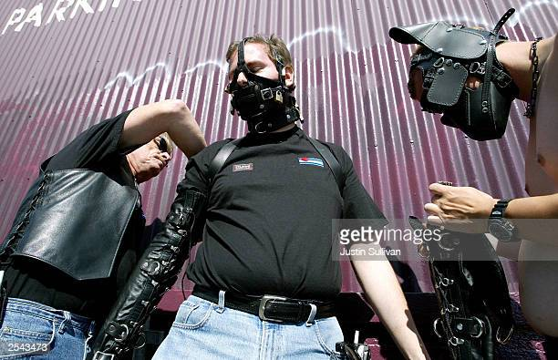 Kenneth Lareau of Tracy California is helped with his leather bondage costume by Dennis Rector and Matthew Campbell at the 20th Annual Folsom Street...