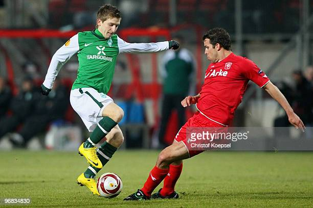 Kenneth Perez of Enschede tackles Marko Marin of Bremen during the UEFA Europa League knockout round first leg match between FC Twente Enschede and...