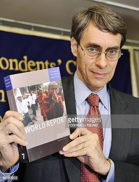 Kenneth Roth executive director of Human Rights Watch shows its annual report during a press conference in Tokyo on March 18 2008 Roth called for...