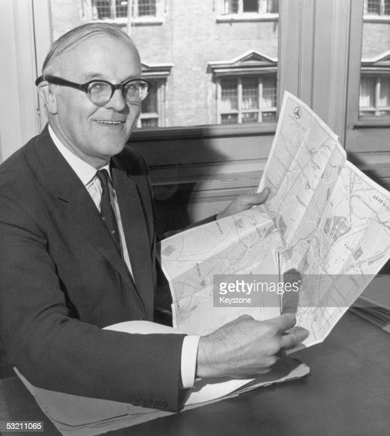 Kenneth Sandilands Duncan General Secretary of the British Olympic Association from 1949 to 1975 studies a map of Tokyo before the upcoming Olympics...