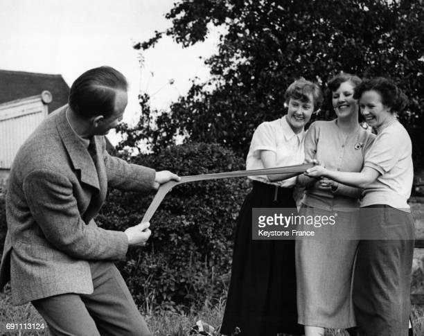 Kenneth Trent tire sur un bas nylon maintenu à l'autre extrémité par trois membres de son personnel pour démontrer la résistance du nylon qu'il...