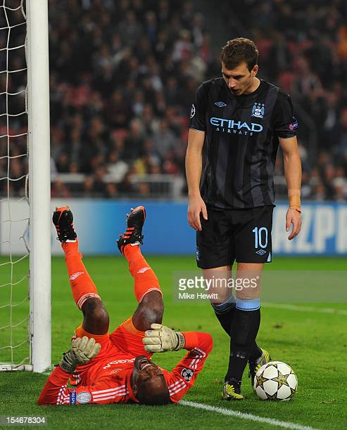 Kenneth Vermeer of Ajax feels the force of a challenge from Edin Dzeko of Manchester City during the UEFA Champions League Group D match between AFC...