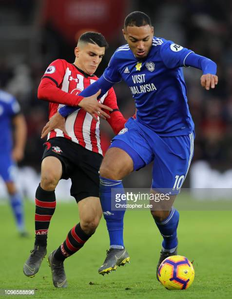 Kenneth Zohore of Cardiff City runs with the ball under pressure from Mohamed Elyounoussi of Southampton during the Premier League match between...