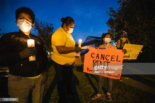 Kennia Viera, center, of Los Angeles, who is a single mom, unemployed and in danger of being evicted at the end of January, protests with her kids,...