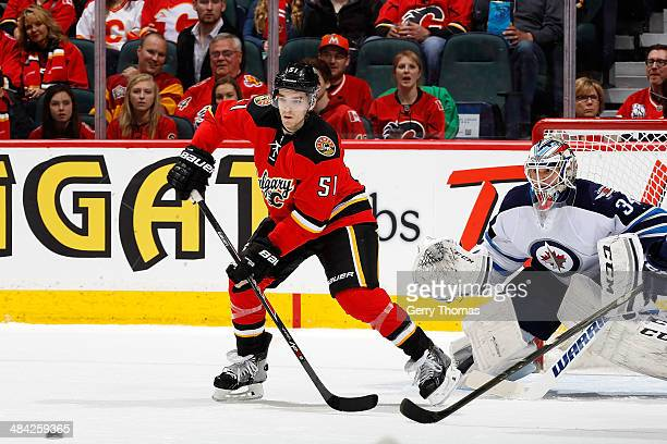 Kenny Agostino of the Calgary Flames looks to tip the puck past Michael Hutchinson of the Winnipeg Jets at Scotiabank Saddledome on April 11 2014 in...