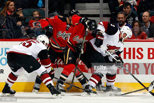 Kenny Agostino of the Calgary Flames skates against Nicklas Grossman of the Arizona Coyotes during an NHL game at Scotiabank Saddledome on March 11...