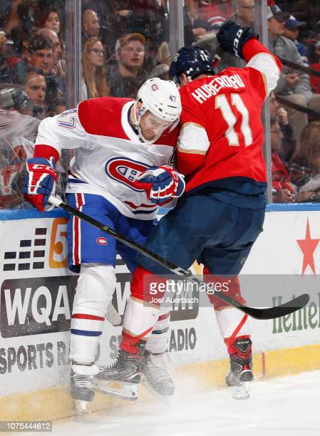 Kenny Agostino of the Montreal Canadiens and Jonathan Huberdeau of the Florida Panthers battle for control of the puck behind the net during second...