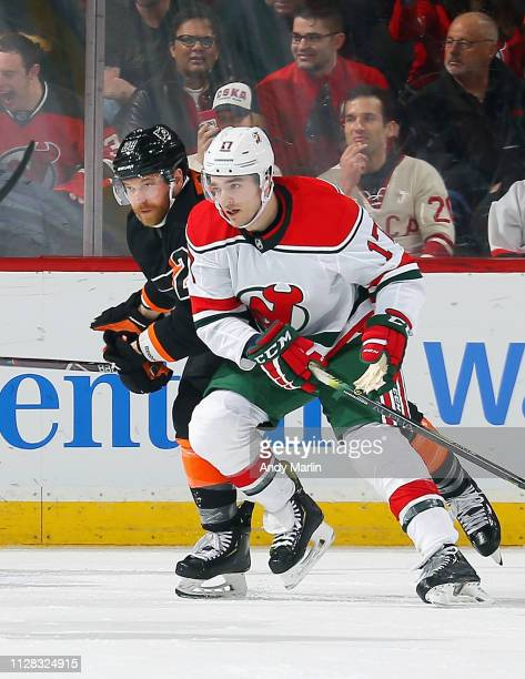Kenny Agostino of the New Jersey Devils and Claude Giroux of the Philadelphia Flyers battles for position during the game at Prudential Center on...