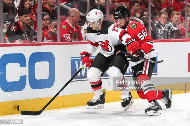 Kenny Agostino of the New Jersey Devils and Erik Gustafsson of the Chicago Blackhawks chase the puck in the third period at the United Center on...
