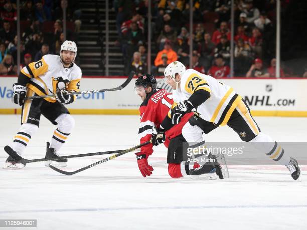 Kenny Agostino of the New Jersey Devils and Jack Johnson of the Pittsburgh Penguins skate during the third period at the Prudential Center on...