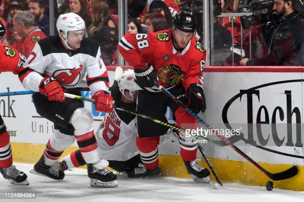 Kenny Agostino of the New Jersey Devils and Slater Koekkoek of the Chicago Blackhawks chase the puck in the second period at the United Center on...