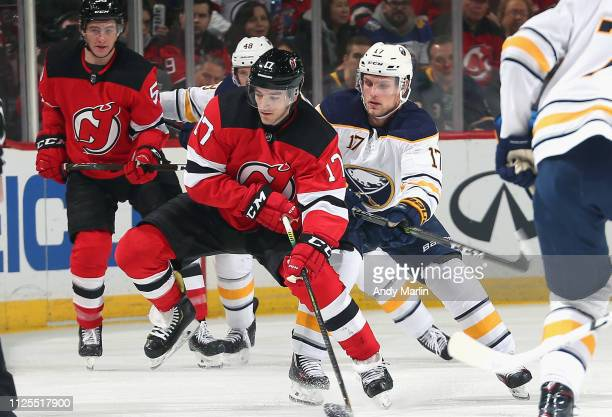 Kenny Agostino of the New Jersey Devils and Vladamir Sobotka of the Buffalo Sabres battle for position during the game at Prudential Center on...