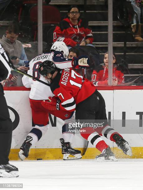Kenny Agostino of the New Jersey Devils checks Zach Werenski of the Columbus Blue Jackets during overtime at the Prudential Center on March 5 2019 in...