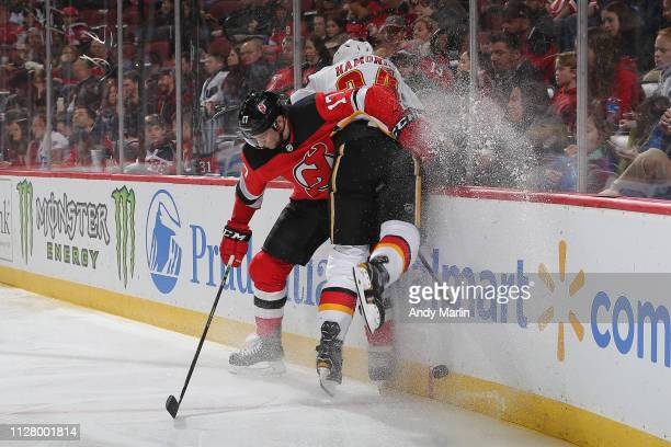Kenny Agostino of the New Jersey Devils gets tangled up with Travis Hamonic of the Calgary Flames during the game at Prudential Center on February 27...