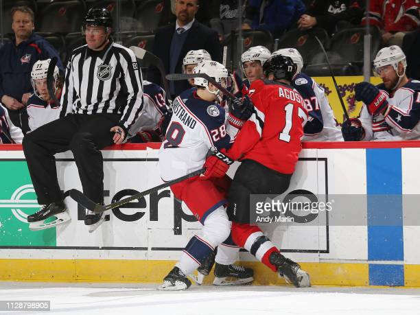 Kenny Agostino of the New Jersey Devils is checked by Oliver Bjorkstrand of the Columbus Blue Jackets during the third period at the Prudential...