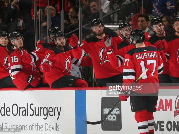 Kenny Agostino of the New Jersey Devils is congratulated as he returns to the bench after scoring a goal during the first period against the...