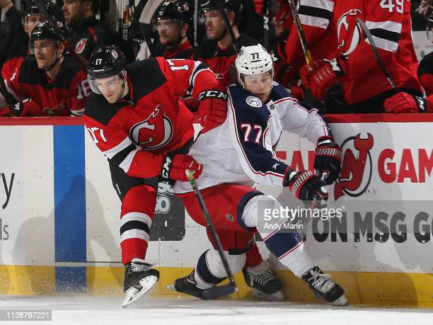 Kenny Agostino of the New Jersey Devils skates against Josh Anderson of the Columbus Blue Jackets during the first period at the Prudential Center on...