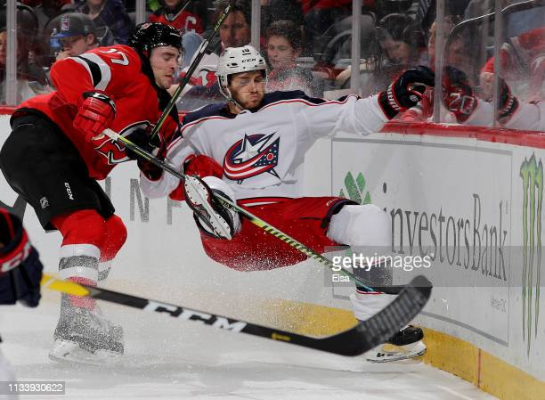 Kenny Agostino of the New Jersey Devils trips up Alexander Wennberg of the Columbus Blue Jackets on March 05 2019 at Prudential Center in Newark New...