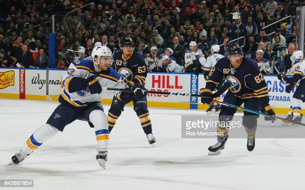 Kenny Agostino of the St Louis Blues fires a backhand shot while being defended by Tyler Ennis and Marcus Foligno of the Buffalo Sabres during an NHL...