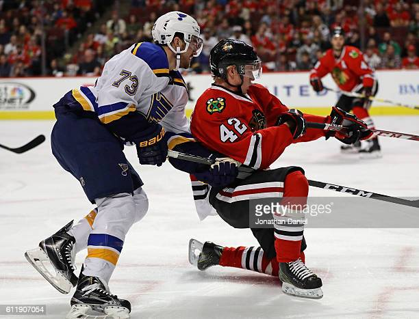 Kenny Agostino of the St Louis Blues gets called for hooking against Gustav Forsling of the Chicago Blackhawks during a preseason game at the United...